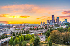 Seattle-Skyline und zwischenstaatliche Autobahnen laufen mit Elliott Bay und dem Ufergegendhintergrund in der Sonnenuntergangzeit Lizenzfreie Stockbilder