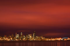Seattle skyline under fiery dawn sky. Seattle, WA, USA Dec. 8, 2011: City skyline of Seattle, Washington still has its lights on as a fiery dawn breaks over Royalty Free Stock Image