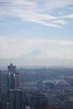 Seattle View of Mt. Rainier. A view of Mt. Rainier through light fog, with the city of Seattle, Washington, in the foreground Stock Photo