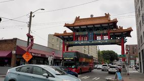 Seattle historic Chinatown Gate on an overcast day with traffic and onlookers stock video footage