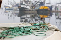 SEATTLE, WA - OCTOBER 28, 2017: Fishermen`s terminal. SEATTLE, WA - OCTOBER 28, 2017: Close-up of the marine rope on a jetty with fishing boats on the blurred Royalty Free Stock Image