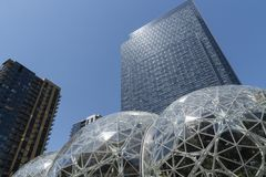 Amazon World Headquarters sunny day with condo tower. Seattle, Washington circa May 2018 the Amazon company world headquarters with Spheres terrariums and royalty free stock photo