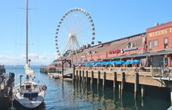 Seattle, Washington, 9/14/17, den Seattle strandrestaurangen med en ansluten segelbåt och det stort rullar in bachgrounden Royaltyfri Foto
