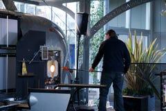 SEATTLE, WASHINGTON, los E.E.U.U. - 23 de enero de 2017: Un hombre toma motlen el vidrio y formas él usando algunas herramientas  fotografía de archivo