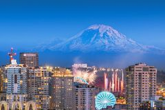 Seattle, Washington, USA downtown skyline with Mt. Rainier. And a fireworks show below royalty free stock image