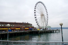 SEATTLE, WASHINGTON, USA - JAN 25th, 2017: Looking Down the Docks of the Pier District with the Great Wheel in the Stock Images