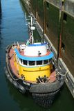 Small tugboat in Lock. SEATTLE, WASHINGTON, USA JULY 7, 2017: Small red, yellow, and blue tug boat enters the small lock at Hiram Chittenden Locks Ballard Locks Stock Photos