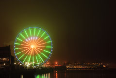 Seattle Wheel Blue Friday Pre Superbowl. Seattle's Great Wheel in Seahawks Colors with a football on Blue Friday and ferry docked stock images