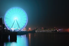 Seattle Wheel Blue Friday Pre Superbowl. Seattle's Great Wheel in Seahawks Colors with a football on Blue Friday and ferry docked stock image