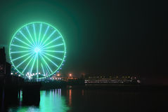 Seattle Wheel Blue Friday Pre Superbowl. Seattle's Great Wheel in Seahawks Colors with a football on Blue Friday and ferry docked stock photos