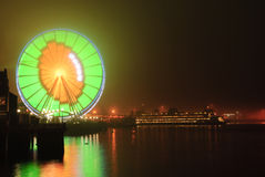 Seattle Wheel Blue Friday Pre Superbowl. Seattles Great Wheel in Seahawks Colors with a football on Blue Friday with a ferry in the background royalty free stock photos
