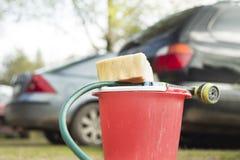 Seau, éponge et tuyau d'arrosage sur le fond des voitures Images stock