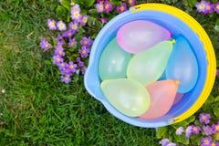 Seau bleu avec des ballons d'eau images stock