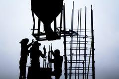 Seau concret au-dessus des travailleurs dans le chantier de construction Images libres de droits