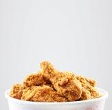 Seau croustillant de poulet frit du Kentucky à un arrière-plan blanc Photographie stock libre de droits