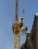 Seau de ciment d'ascenseur de grue à tour jusqu'au dessus du bâtiment Photo libre de droits