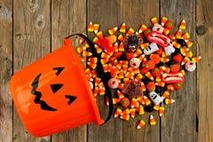 Seau de lanterne de Halloween Jack o avec renverser la sucrerie au-dessus du bois Photos libres de droits