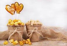 Seau de papier de maïs éclaté et d'arachides de caramel Lucette deux sous forme de coeur Photos libres de droits