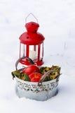 Seau de pommes et lanterne rouge sur la neige Photographie stock