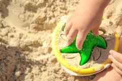 Seau jaune en plastique coloré et lumineux et étoile verte dans des mains du ` s d'enfant sur le fond du jeu du ` s de sable de m Image libre de droits
