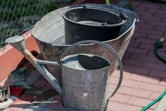 Seaux d'arrosage dans le jardin Image de jardinage de concept avec le seau en métal pour l'eau photographie stock