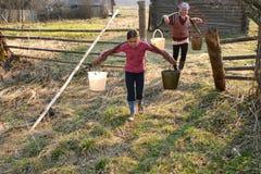Seaux d'eau de transport de fille russe d'agriculteur Images libres de droits