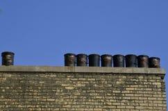 Seaux noirs de goudron plaçant sur le rebord de toit Photo libre de droits