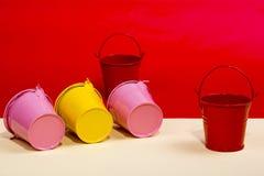 Seaux roses, rouges et jaunes Photographie stock libre de droits