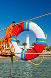 Seaview of lighthouse through bright lifebuoy Royalty Free Stock Photos