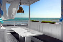 Seaview Restaurant Interior. White Terrace With Wooden Furniture Stock Photos
