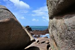 Seaview between rocks at the pink granite coast near Perros Guirec in Brittany France stock image