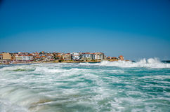 Seaview with waves. And old town on background Stock Photography