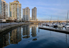 Seawall and boats in city marina. Stock Images