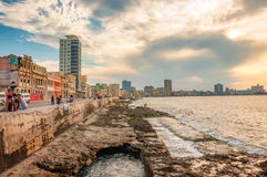 Seawall at Malecon Promenade, Old Havana, Cuba. Havana, Cuba - March 6, 2016: People gather almost every evening to see the sunset or just walking and fishing Stock Images