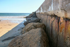 Seawall. A weather-beaten seawall protects a boating channel by a beach in California Royalty Free Stock Photos