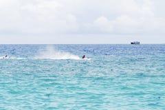 Seawater krajobraz z ładunku statkiem na horyzoncie i łodzi motorowa Zdjęcia Royalty Free