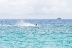 Seawater landscape with cargo ship on horizon and speedboat. Sea view of boats and sailors. Motor boats race in sea. Marine racing championship. High speed Royalty Free Stock Photos
