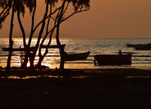 Sunset with fishing boats & others. Beautiful seawater of Bay of Bengal with the couple of fishing boats parked around it royalty free stock photos