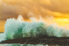 Seawater Waves Splashing on Black Rock during Golden Hour Stock Photos