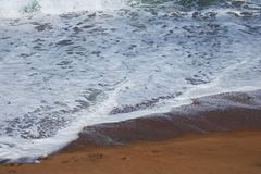 FOAMY SEAWATER ON THE SAND Stock Images