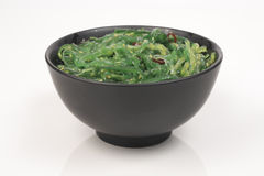 Seaweed salad. Bowl in black on a light background Stock Image