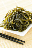 Seaweed salad. Plate of wakame seaweed salad with chopsticks Stock Photo