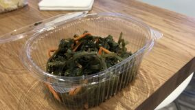 Seaweed salad with carrots in a plastic disposable container at fast food café