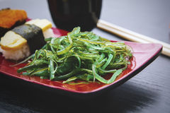 Seaweed salad with sushi on the plate Royalty Free Stock Photo