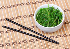 Seaweed with sesame seeds with chopsticks in ceramic bowl on bamboo mat. Chuka salad. Royalty Free Stock Images