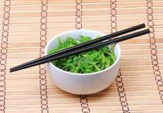 Seaweed with sesame seeds with chopsticks in ceramic bowl on bamboo mat. Chuka salad. Stock Photos