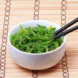 Seaweed with sesame seeds with chopsticks in ceramic bowl on bamboo mat. Chuka salad. Royalty Free Stock Photos