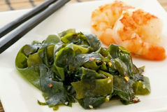 Seaweed with Shrimps. Healthy seaweed with fresh shrimps on a white plate with chopsticks royalty free stock photos