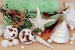 Seaweed Spa. Accessories with bath bombs, towels, sea shells and pearls over bamboo background Stock Image