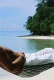 Secção mestra do homem que encontra-se no hammock na praia Fotografia de Stock Royalty Free